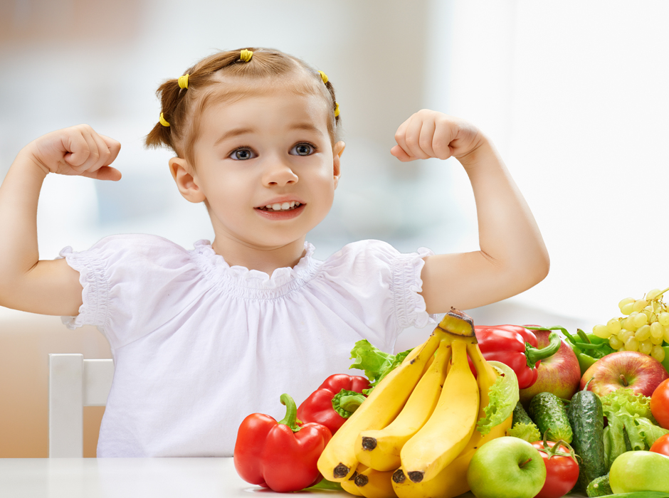 girl showing muscles in front of fruits and vegetables