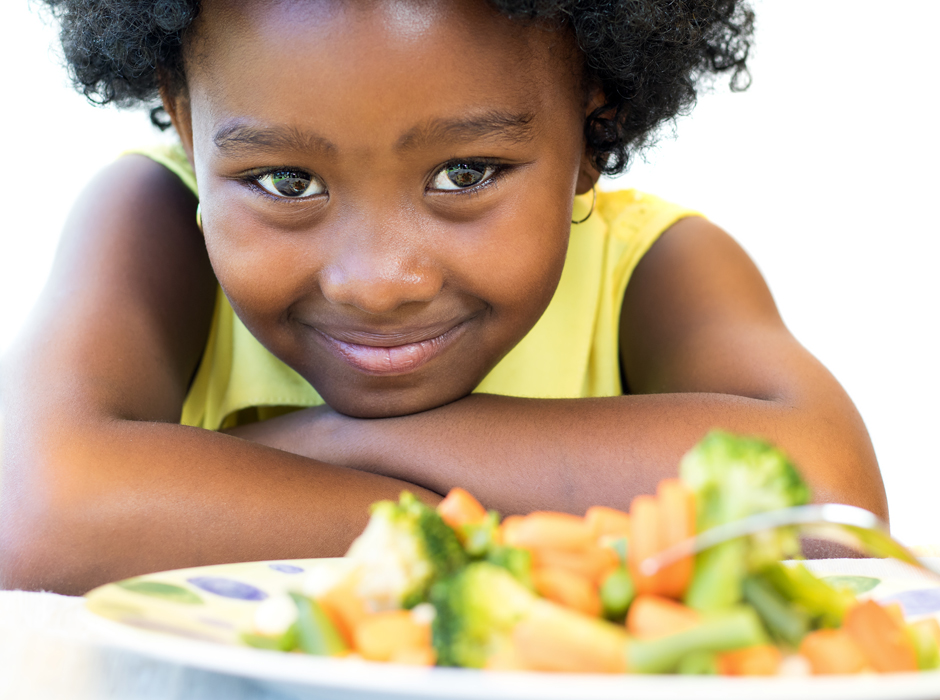 cute young african american girl with a plate of vegetables