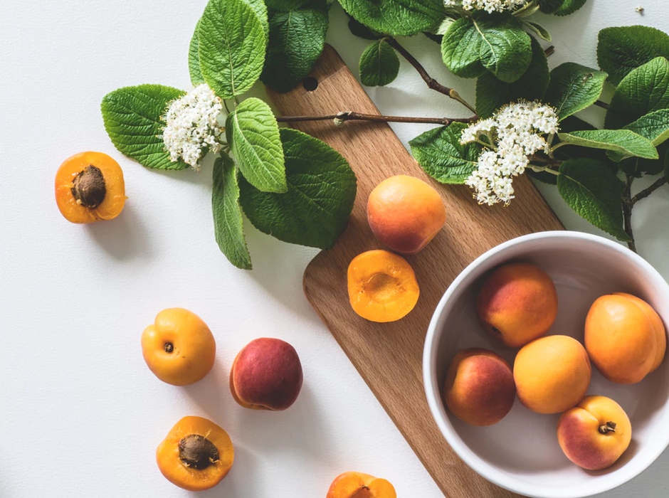 peaches in a bowl and on the counter with white flowers beside them
